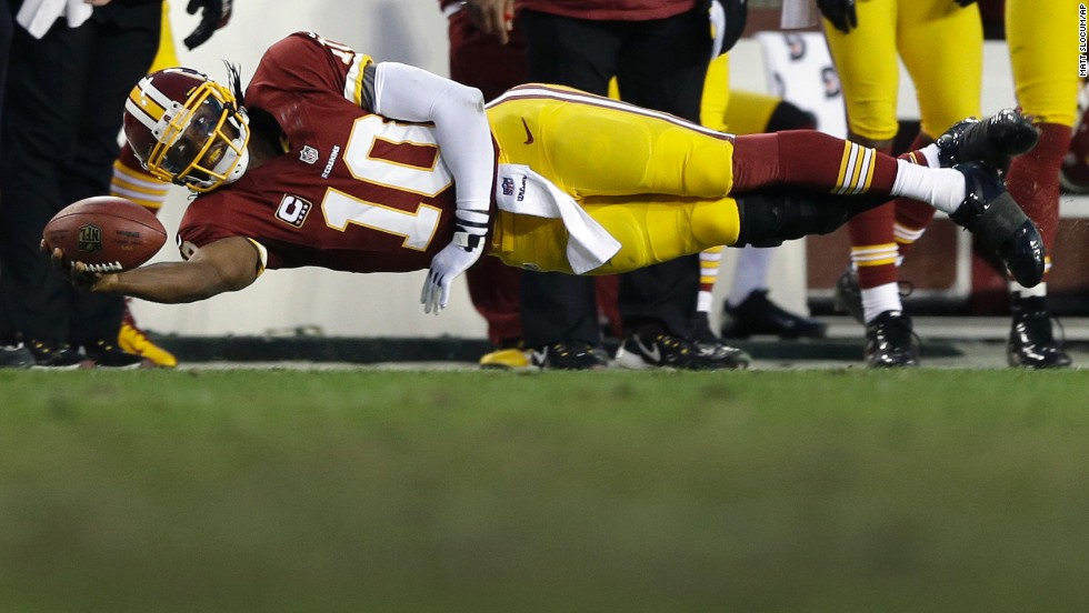Washington Redskins quarterback Robert Griffin III dives on a quarterback keeper during the first half of an NFL wild card playoff game against the Seattle Seahawks on January 6 in Landover, Maryland. The Seahawks won 24-14.