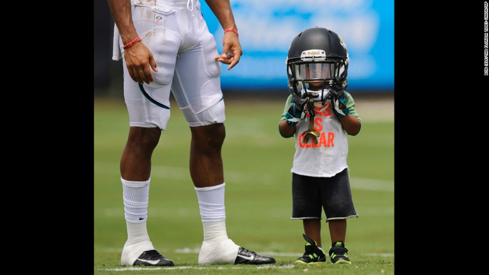 Two-year-old Cecil Shorts IV wears the helmet of his father, Jacksonville Jaguars wide receiver Cecil Shorts III, during NFL training camp on July 31 in Jacksonville, Florida.