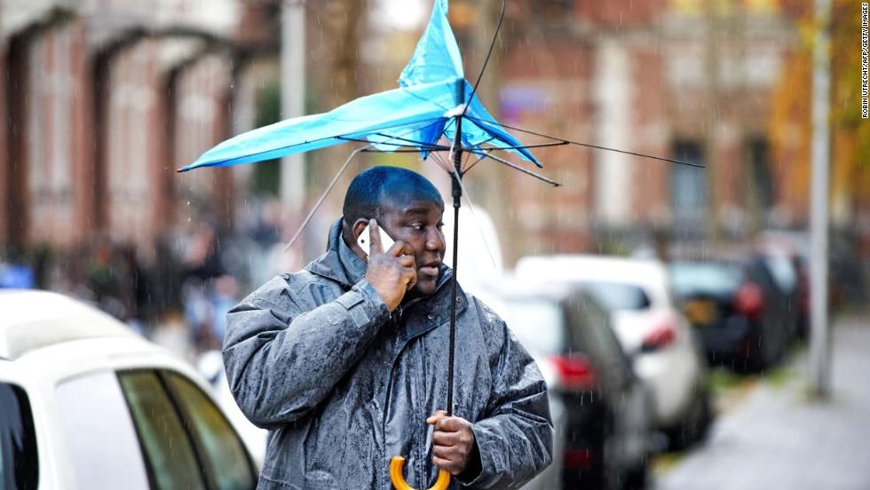 A man walks with a broken umbrella December 5 in Utrecht, Netherlands.