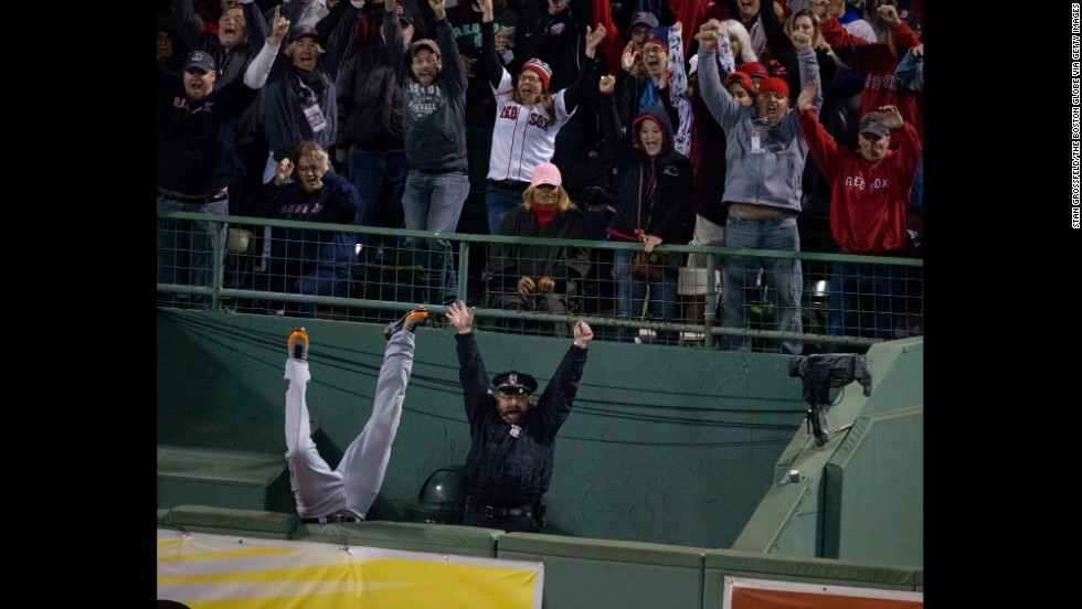 Torii Hunter of the Detroit Tigers falls into the bullpen while trying to catch a homerun ball hit by David Ortiz of the Boston Red Sox to tie the game in the eighth inning at Fenway Park in Boston on October 13. The Red Sox defeated the Tigers 6-5 in Game 2 of the American League Championship Series.
