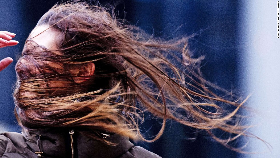 A woman struggles against the wind in Rotterdam, Netherlands, on Thursday, December 5. Large storms with gale winds up to 90 mph are moving across northwestern Europe, causing disruptions in rail and road traffic.