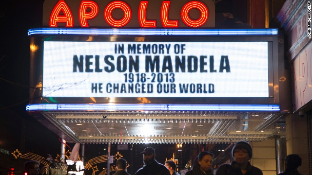 Pedestrians pass beneath the Apollo Theatre marquee commemorating Mandela on December 5 in the Harlem neighborhood of New York.