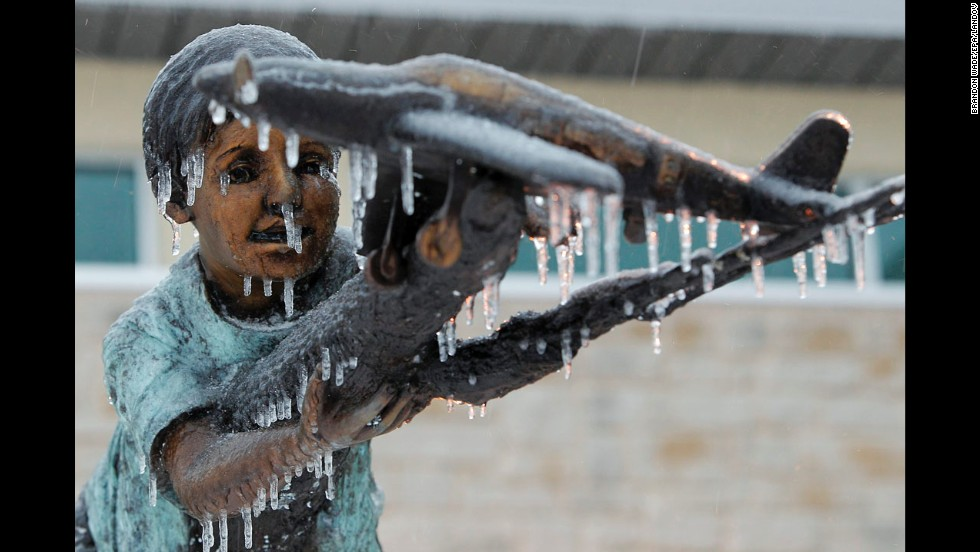 A bronze statue is covered in ice December 6 at Grand Prairie Municipal Airport in Grand Prairie, Texas.