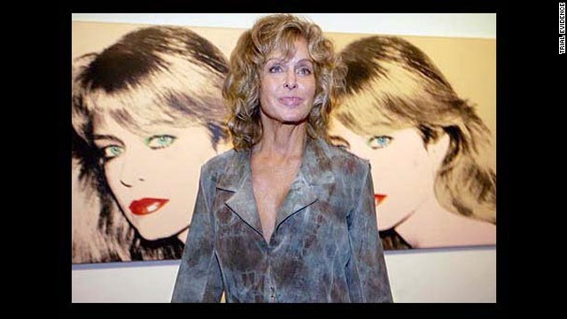 Farrah Fawcett posed with two Andy Warhol prints of her at the Warhol Museum in Pittsburgh.