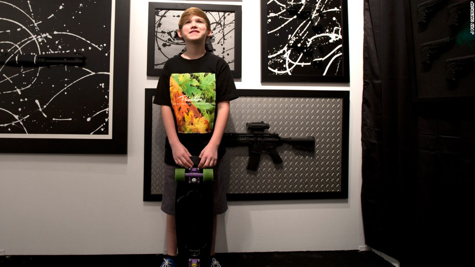 Charles Gitnick poses with his artwork during his Art Basel show in Miami, December 4. The 11-year-old is one of the youngest artists showing at Art Basel. Gitnick places realistic toy guns on canvas and paints over them, purposely camouflaging them in an abstract design. He says it's his way to express his fear of gun violence.