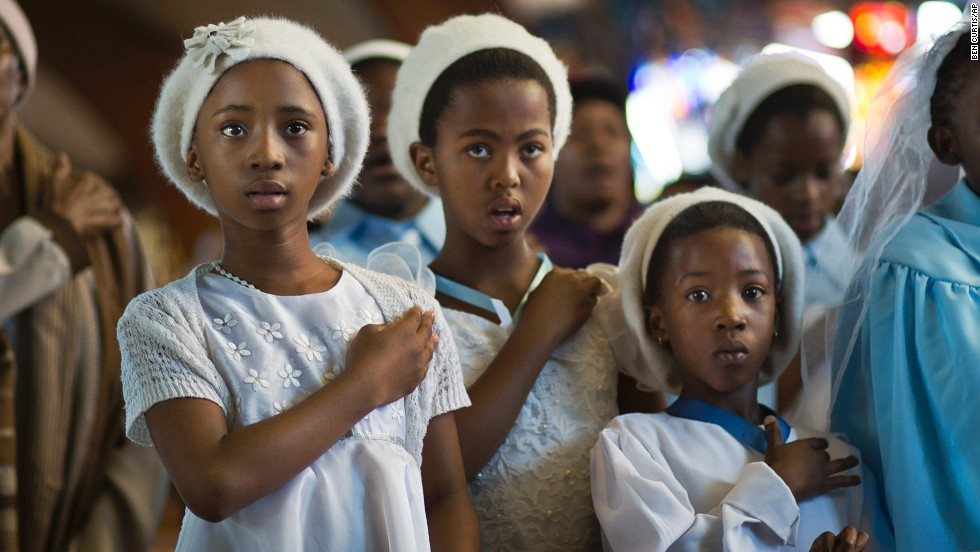 Young choir members attend a morning Mass on December 8 in memory of Mandela at the Regina Mundi Catholic Church, one of the focal points of the anti-apartheid struggle, in the Soweto district of Johannesburg. South Africans flocked to houses of worship for a national day of prayer and reflection to honor Mandela.