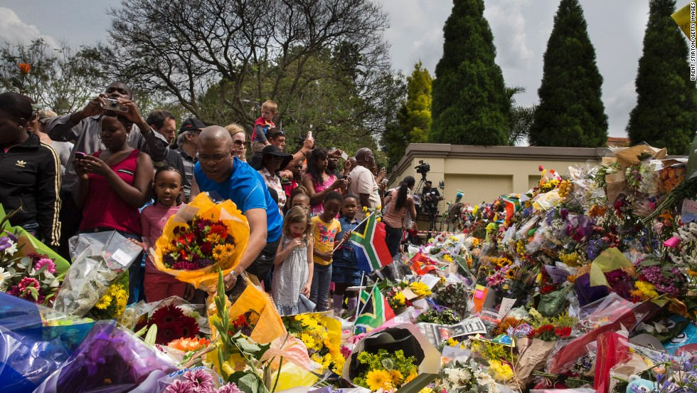 Crowds of people pay tribute to Mandela outside his Johannesburg home on December 7.