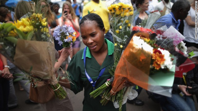 A groundskeeper collects bouquets left at the home of former South African President Nelson Mandela in Johannesburg, South Africa, on Monday, December 9.