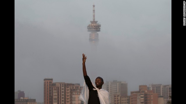 A man prays on a hill overlooking the city of Johannesburg, South Africa, on Sunday, December 8.