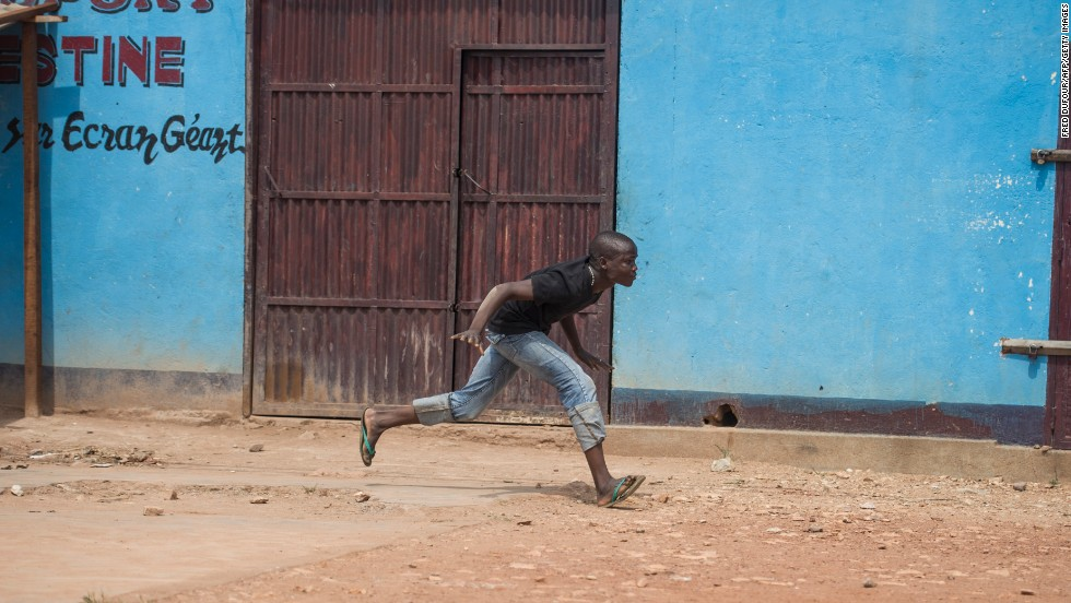 A man runs from gunfire December 9 during a disarmament operation by French soldiers in Bangui.