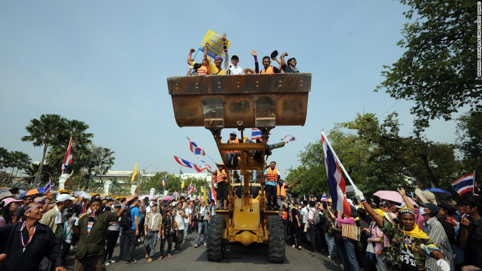 Anti-government protesters celebrate after removing concrete barricades outside the Government House in Bangkok on December 9.
