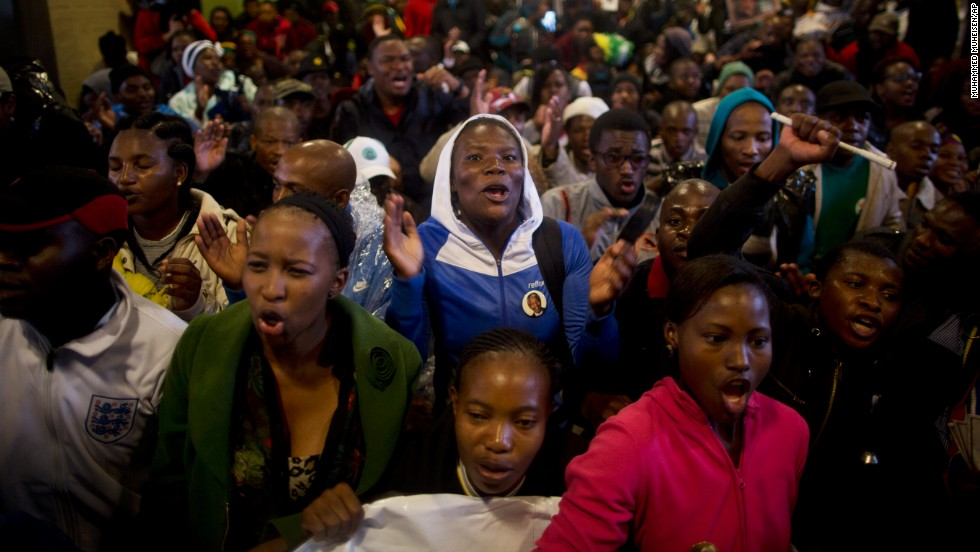 Mourners sing as they take shelter from the rain in the hallways of FNB Stadium.