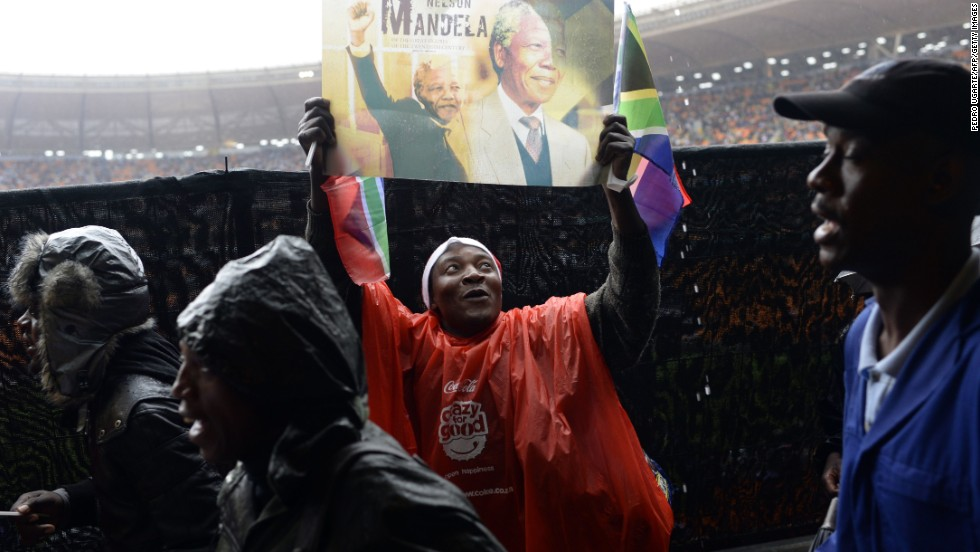 A man displays a sign with pictures of Mandela during the memorial service.