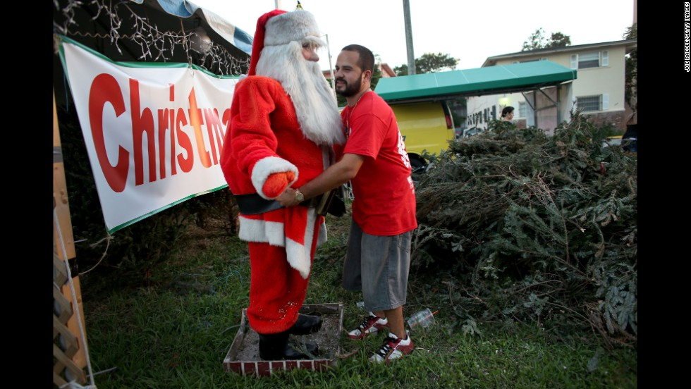 Anthony Martinez, owner of a Miami Christmas tree lot, adjusts the outfit on a Santa Claus mannequin while waiting for customers December 9.