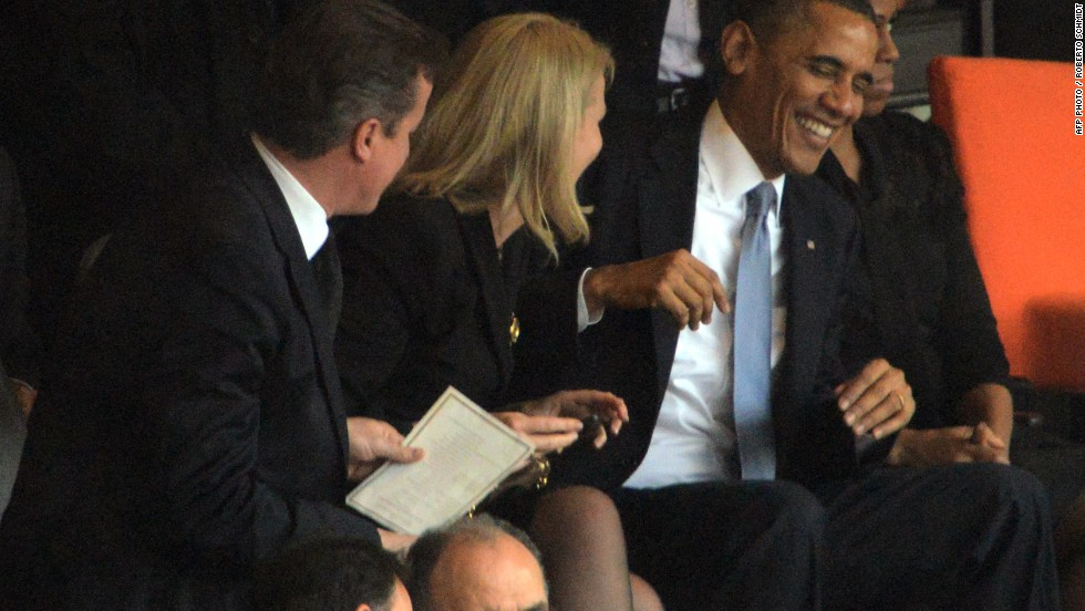 Danish Prime Minister Helle Thorning-Schmidt shares a joke with U.S. President Barack Obama at the Nelson Mandela memorial as UK Prime Minister David Cameron looks on.