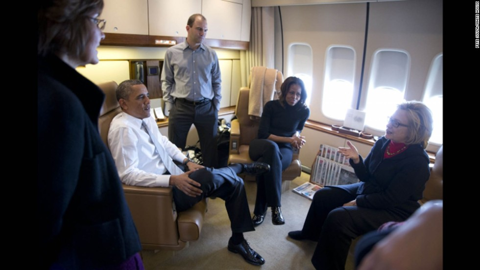 Former Secretary of State Hillary Clinton talks with the Obamas, speechwriter Ben Rhodes and former Chief of Protocol Capricia Marshall aboard Air Force One.