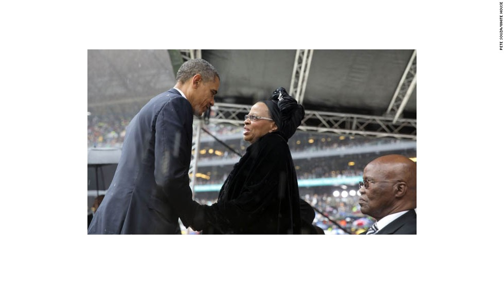 President Obama greets Mandela's widow Graca Machel after speaking at the memorial service.