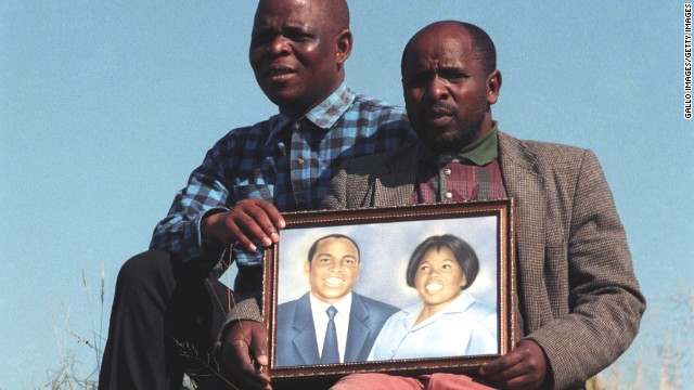 The brothers of Griffiths Mxenge hold up a picture of him and his wife, Victoria. Both Griffiths, a human rights lawyer, and Victoria, were brutally murdered by the apartheid security police.