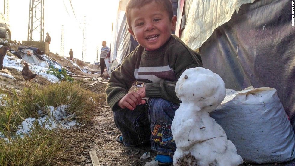 "DECEMBER 13 - BEKAA VALLEY, LEBANON:  A young Syrian refugee proudly presents his snowman to CNN's Christian Streib. Severe winter storms have only <a href=""http://edition.cnn.com/video/data/2.0/video/world/2013/12/11/pkg-paton-walsh-syria-winter.cnn.html"">worsened conditions at makeshift refugee camps</a>. 125,000 refugees are living in freezing conditions in tents in the Bekaa region, but many, like this little boy, are determined to make the best of the situation."