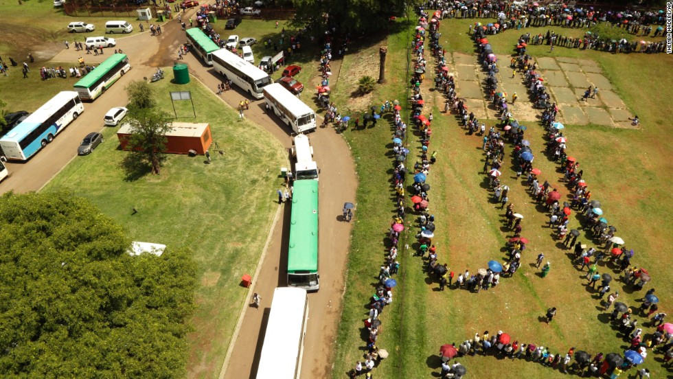 People queue to catch a bus to see the remains of Nelson Mandela at the Union Buildings on December 12.