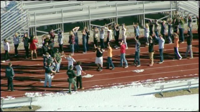 Persons evacuated from Arapahoe High School in Centenial, Colorado walk on the school's track after a shooting at the school.