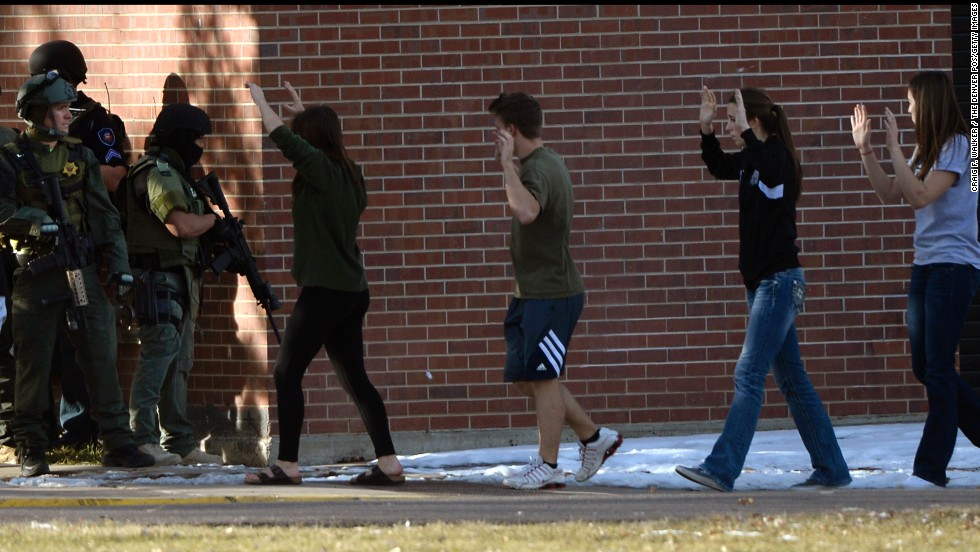 Students are escorted out of Arapahoe High School in Centennial, Colorado, on December 13.