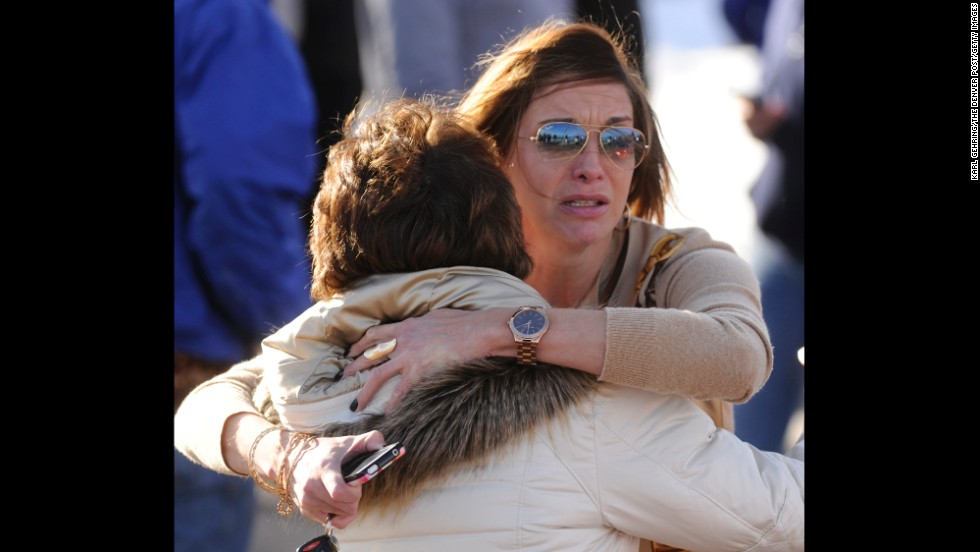 Parents Cathy Thorson, left, and Heather Moran, facing the camera, embrace while they wait for news on their children.