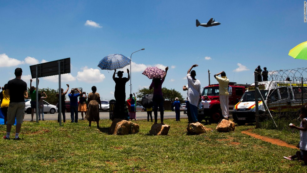 People wave at the aircraft carrying the casket of Mandela as it takes off from Waterkloof air base on the outskirts of Pretoria, South Africa.