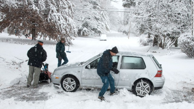 Dave Andsager, right, kicks snow out from under his car on in Champaign, Illinois, as neighbors Andy Dixon, left, and Dave Mattson help him dig his car out on December 14.