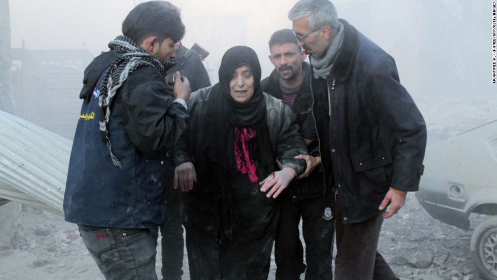 Syrians help a wounded woman following airstrikes in Aleppo on December 15.