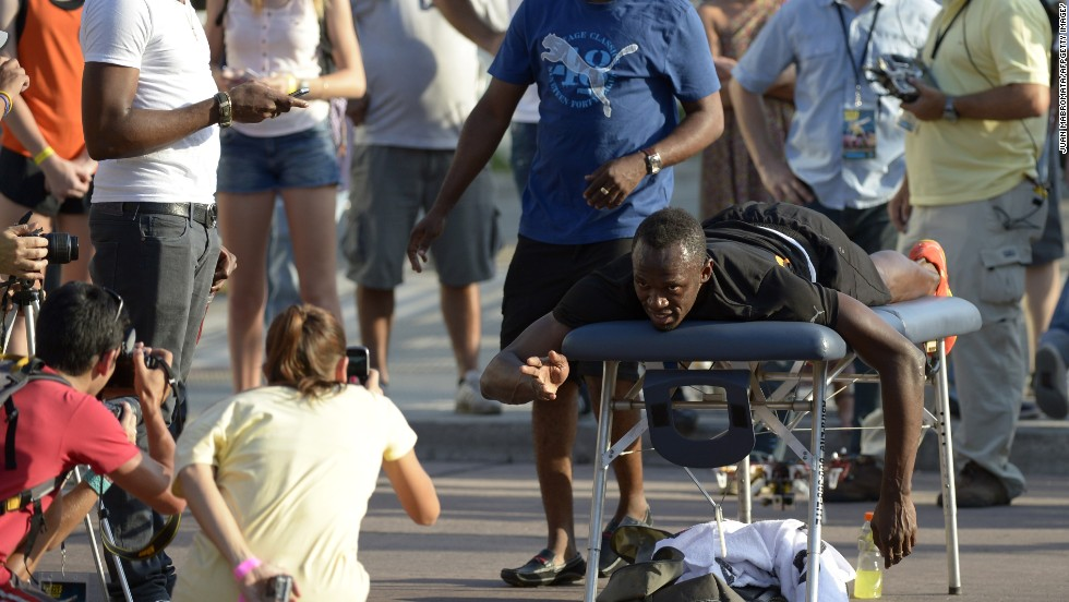 Bolt poses for photos while having a massage prior to the race, on the famous 9th of July Avenue in Buenos Aires, and told reporters he was aiming to defend his three Olympic titles in Rio 2016.