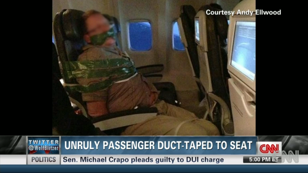 """A photo of man a bound to his seat on an Iceland Air flight made social media rounds. The man, apparently inebriated, was """"hitting, screaming and spitting at other passengers,"""" said the airline, adding that duct tape and plastic zip ties are standard protocol when restraining unruly passengers."""