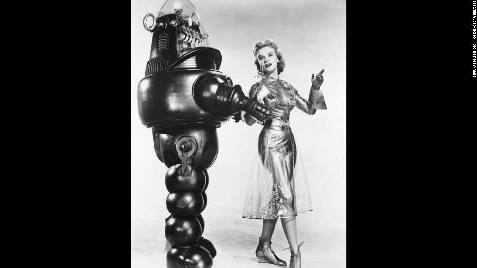 "American actress Anne Francis as Altaira 'Alta' Morbius poses with Robby the Robot in a promotional portrait for ""Forbidden Planet"" in 1956."