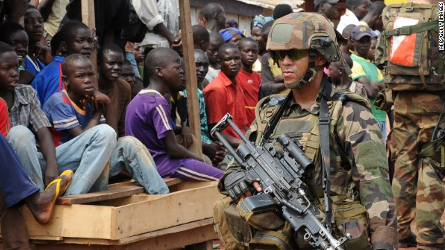 Young people watch as French soldiers of the Sangaris operation patrol on December 10, 2013 in the North of Bangui, Central African Republic.