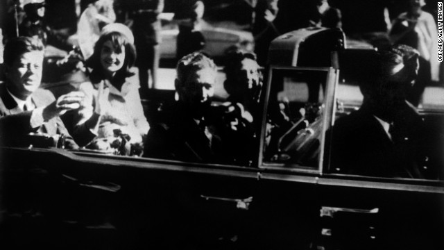 President John F. Kennedy and the first lady ride in an open-top limo in Dallas just moments before the assassination.