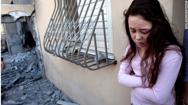 An Israeli girl stands outside her house after it was hit by a rocket fired from Gaza in November last year in Beersheba, Israel.