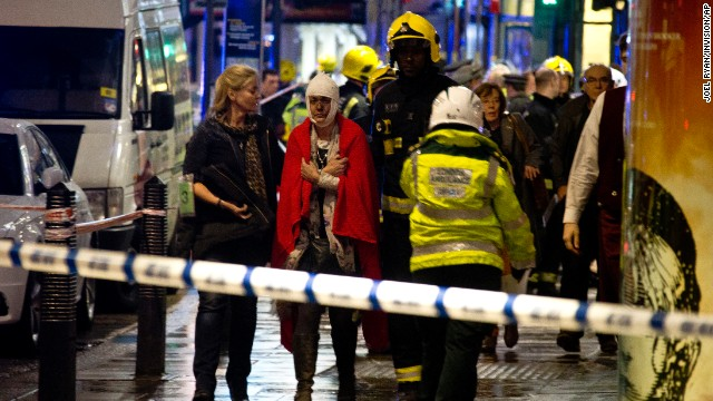 "A woman stands bandaged and wearing a blanket  given by emergency services  following an incident at the Apollo Theatre, in London's Shaftesbury Avenue, Thursday evening, Dec. 19, 2013, during a performance at the height of the Christmas season, with police saying there were ""a number"" of casualties. It wasn't immediately clear if the roof, ceiling or balcony had collapsed  during a performance. Police said they ""are aware of a number of casualties,"" but had no further details. (AP Photo by Joel Ryan, Invision)"