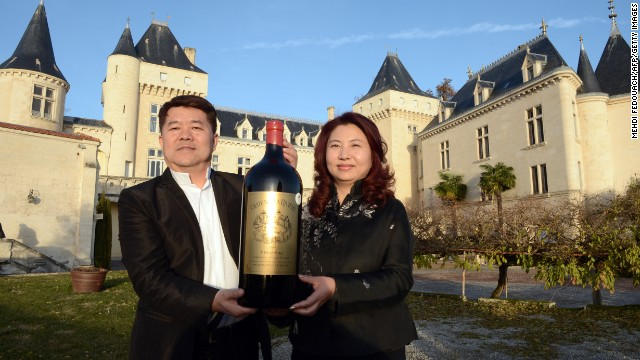 Lam Kok and his wife pose for a photograph Friday in front of the Chateau de La Riviere, in La Riviere.