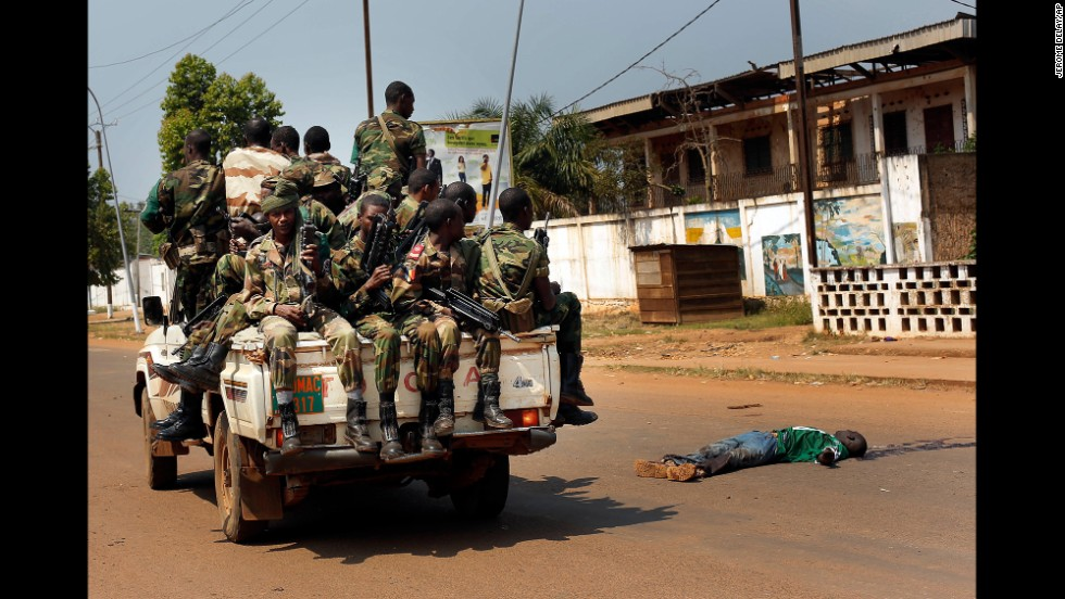 <strong>December 20:</strong> Chadian troops from a multinational African peacekeeping force drive past the body of a man who was suspected of having been an ex-Seleka militiaman, in Bangui, the capital of the violence-wracked Central African Republic.