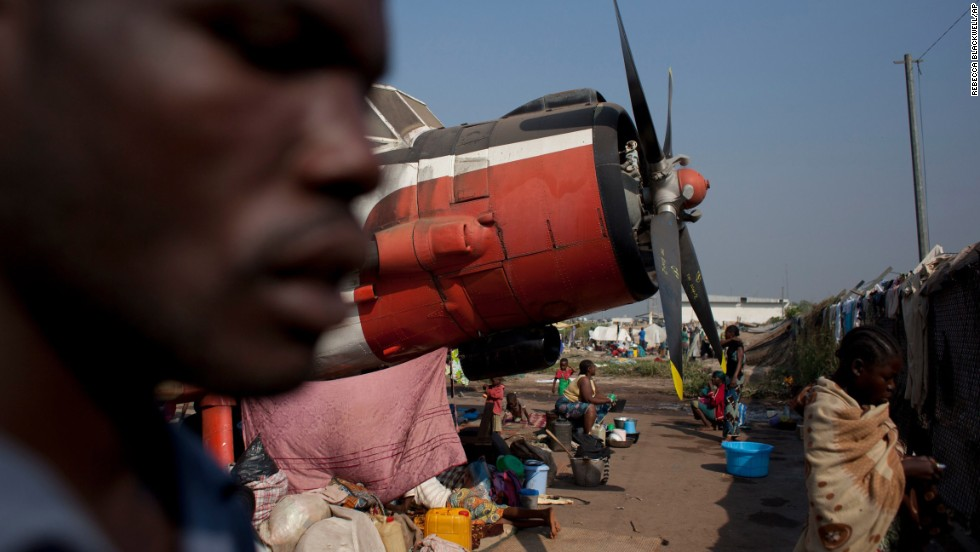 Displaced people sit with their belongings at a makeshift camp housing thousands in Bangui on Saturday, December 21.
