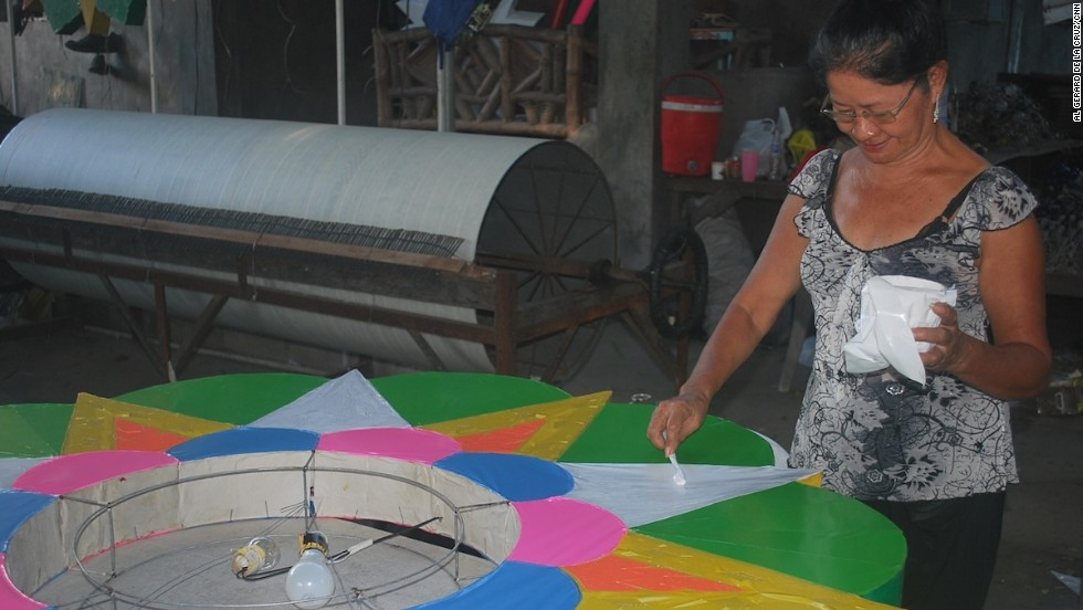 An employee in Quiwa's workshop puts the finishing touches on a small parol ordered by a school in Manila. In the background is an unfinished 'rotor,' a steel drum that serves as the light switch on a giant parol.