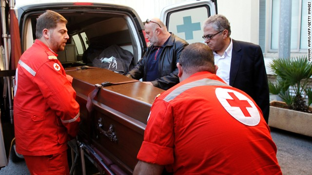 Members of the Lebanese Red Cross carry the coffin of Abbas Khan, a British doctor who died in a Syrian jail, as it arrives in Beirut on December 21, 2013.