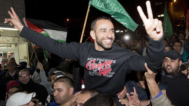 """Palestinian prisoner Samer al-Issawi, who held a hunger strike for several months, flashes the """"V"""" for victory sign as he celebrates his release from an Israeli jail in the Arab Jerusalem neighbourhood of Issawiya, on December 23 2013. AFP PHOTO/AHMAD GHARABLIAHMAD GHARABLI/AFP/Getty Images"""