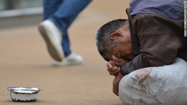 """A man begs on a street in Shanghai on May 22, 2013. China has cut its """"extreme poverty"""" rate by nearly three-quarters."""