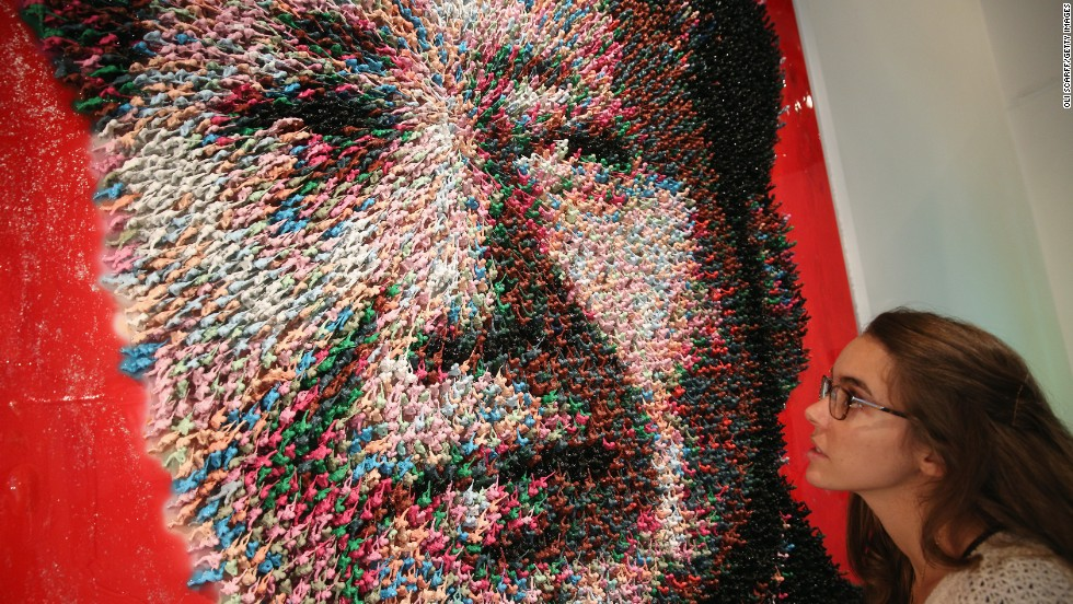 A woman admires an artwork by Joe Black of Mao Zedong entitled, 'Workers of the World, Unite!', which is made from 9000 hand-painted toy soldiers, in the Opera Gallery on October 14.