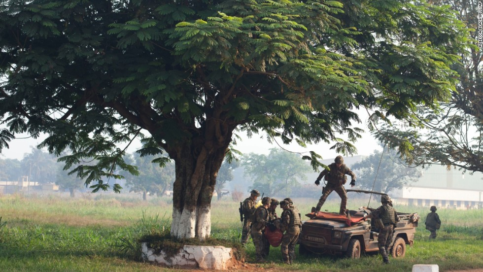 French soldiers load a wounded man onto the front of a military vehicle to get medical help in Bangui on December 23.