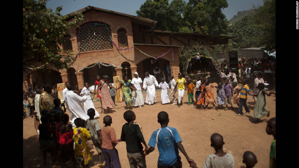 Priests and nuns lead children in a dance at a Bangui, Central African Republic, monastery serving as a camp for those displaced in the African nation's conflict between Christian and Muslim militias.