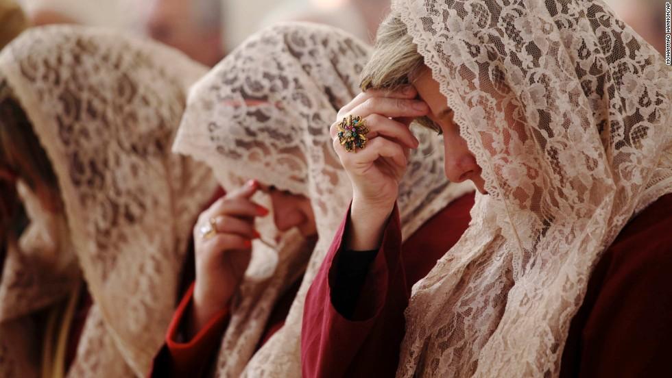 Choir members pray during a morning Mass in Amman, Jordan.