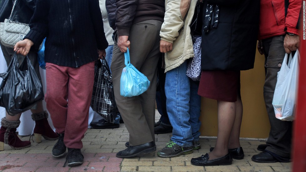People line up to get meals as people in need and homeless gathered in an indoor stadium in Athens, Greece, for a Christmas meal provided by the Athens municipality.