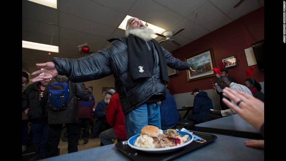 Moses Gibson dances to choir songs after receiving his Christmas Day lunch at the Shepherds of Good Hope in Ottawa, Ontario.
